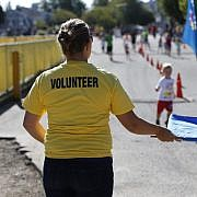 Volunteer waving kids in to the finish